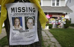 A missing poster still rests on a tree outside the home of Amanda Berry Wednesday, May 8, 2013, in Cleveland.
