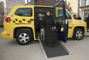 A woman exits the Vehicle Production Group's MV-1 automobile, the first vehicle designed from the ground up to be wheelchair-accessible, in January 2010.