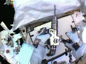 In this image made from video provided by NASA, astronaut Christopher Cassidy, foreground, holds a power wrench as he stows away a suspect coolant pump on the International Space Station.