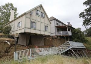 The bedroom carpets hang from the home of Jagtar Singh, left, after the ground gave way in Lakeport, Calif.