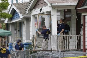 In this Tuesday, May 7, 2013 file photo, members of the FBI evidence response team carry out the front screen door from the house where three women were held captive, in Cleveland.