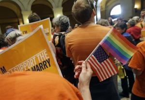 A gay marriage supporter waves the US. flag and a rainbow flag as supporters and opponents of Minnesota's gay marriage bill gather in the State Capitol Rotunda to take up the issue.