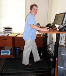 A customer uses a treadmill desk by TreadDesk.