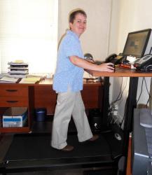 A customer uses a treadmill desk by TreadDesk.