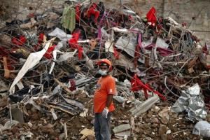 A Bangladeshi rescuer stands amid the rubble during search and recovery efforts Sunday.