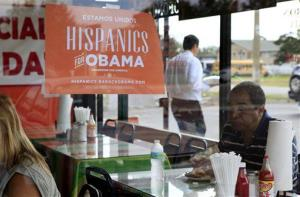 In this Oct. 26, 2012, file photo, Spanish language election campaign signs promoting President Barack Obama hang on the windows at Lechonera El Barrio Restaurant in Orlando, Fla.