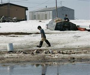 In this May 24, 2006 picture, a boy walks along the banks of the Newtok River in the village of Newtok, Alaska.