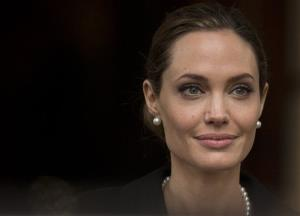 Angelina Jolie looks to the media as she leaves a G8 Foreign Ministers meeting on sexual violence against women in London, Thursday, April, 11, 2013.