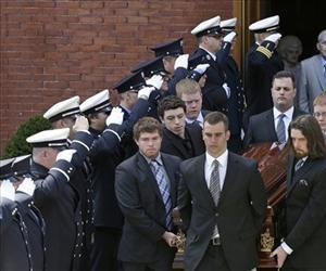 An honor guard from area Fire Departments salutes as pallbearers carry the casket of a Boston Marathon bomb victim from her funeral in Medford, Mass., April 22, 2013.