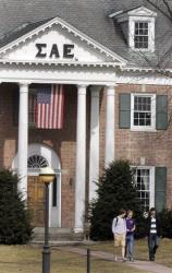 In this photo taken Monday March 12, 2012, students leave the Sigma Alpha Epsilon fraternity on the Dartmouth College campus in Hanover, N.H.