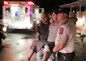 Johnny Ortiz, left, and James South, right, carry Miguel Morales, center, who was injured in a tornado, to an ambulance in Granbury, Texas, on Wednesday, May 15, 2013.