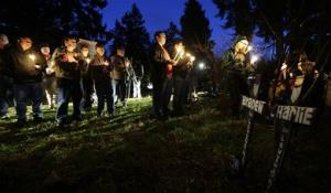 Friends and family hold candles as they stand near crosses placed in memory of Braden and Charlie Powell, Tuesday, Feb. 5, 2013, during a vigil in Graham, Wash.