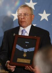 Paul Monti holds up his son's Medal of Honor after it was presented to him by President Barack Obama, who posthumously awarded Army Sgt. 1st. Class Jared C. Monti.