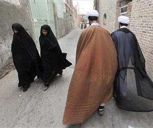 In this picture taken on Tuesday, May 6, 2013, two Iranian clerics, right, and two women walk in an alley of the eastern city of Birjand, Iran.
