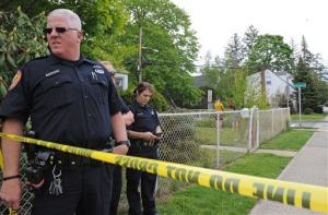 Officers guard the area leading to the house where a Hofstra University student and an armed intruder were killed in Uniondale, NY.