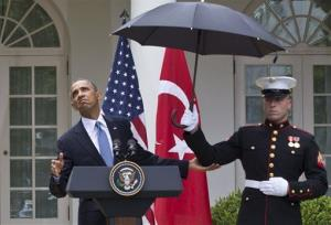 President Barack Obama leans out from under an umbrella to check if it's still raining, during a joint news conference with Turkish Prime Minister Recep Tayyip Erdogan, Thursday, May 16, 2013, in the Rose Garden of the White House in Washington.