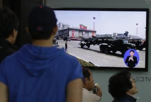 South Koreans watch TV news showing a footage of North Korean missiles on a military parade.