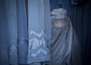 An Afghan woman peers through the  the eye slit of her burqa as she waits to try on a new burqa in a shop in the old town of Kabul, Afghanistan.