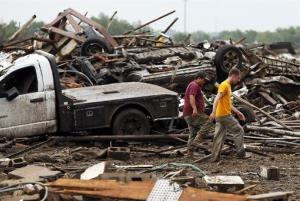 Two men walk through debris in Moore, Oklahoma yesterday.