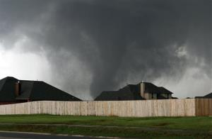 A tornado moves past homes in Moore, Okla., on Monday.