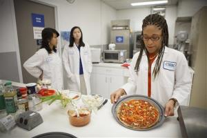 Lockeed Martin senior research scientist Maya Cooper shows a vegan pizza developed at NASA's Advanced Food Technology Project at Johnson Space Center in Houston Tuesday, July 3, 2012. NASA is currently planning a mission to Mars, which has gravity, so more options for food preparation, like chopping vegetables, are available...