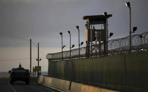 A US trooper stands in the turret of a vehicle with a machine gun, left, as a guard looks out from a tower at the detention facility of Guantanamo Bay US Naval Base in Cuba.