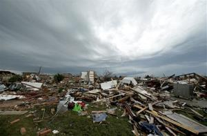 Storm clouds build in the distance beyond tornado-ravaged homes Tuesday, May 21, 2013, in Moore, Okla.