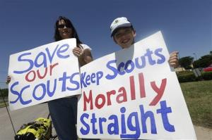 Terri Hall, left, of San Antonio, stands with her son Nathaniel Hall, 8, as they hold signs near where the Boy Scouts of America are holding their annual meeting May 22, 2013, in Grapevine, Texas.