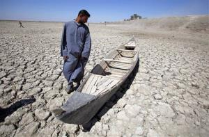 In this photo taken Friday, March 27, 2009, Akeed Abdullah stands next to his boat in a dried marsh in Hor al-Hammar in southern Iraq.
