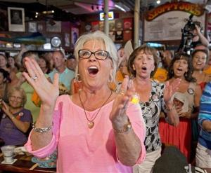 In this Saturday, July 21, 2012 photo, Paula Deen cheers for her husband, Michael Groover, during the semifinals of the Papa Hemingway Look-Alike Contest at Sloppy Joe's Bar in Key West, Fla.