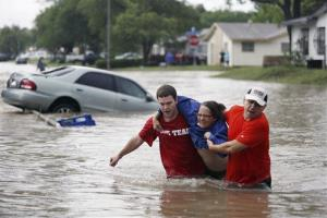 Men help a woman from her car in San Antonio floodwaters.