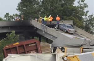 Emergency personnel respond to a train derailment near Rockview, Mo. on Saturday, May 25, 2013. The NTSB launched an investigation into a cargo train collision that collapsed a highway overpass.