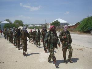 Members of the al-Shabab militant group patrol on foot on the outskirts of Mogadishu.