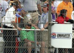 Security personnel assist a fan injured by a broken television camera cable during the NASCAR Sprint Cup series Coca-Cola 600 auto race at Charlotte Motor Speedway yesterday.