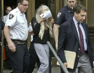 Amanda Bynes, center, wearing sweats and a blonde wig, shields her face as she is escorted after a Manhattan criminal court appearance on May 24, 2013 in New York.