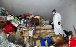 A worker is shown during a cleanup of a hoarder's home in Las Vegas.