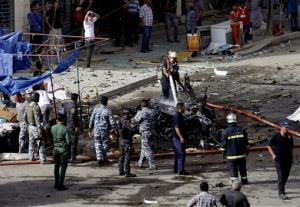 Security forces inspect the scene of a car bomb attack in the Baghdad, Iraq, Monday, May 27, 2013.