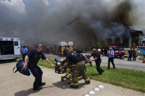 A firefighter is wheeled to an ambulance after fighting a fire at the Southwest Inn Friday in Houston.