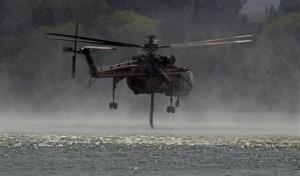 A helicopter pulls water out of Hughes Lake to fight what has been called the Powerhouse fire in Lake Hughes, Calif., late Sunday afternoon, June 2, 2013.