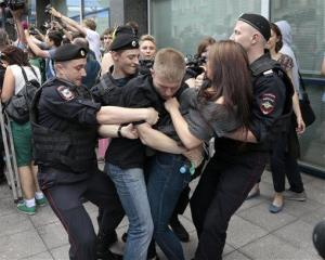 Police officers detain gay rights activists in Moscow yesterday.