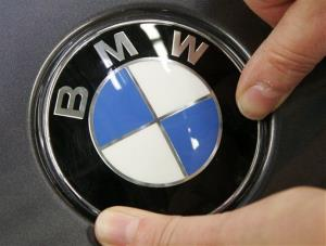 A worker fits the BMW sign at a car in the BMW plant in Leipzig, eastern Germany.