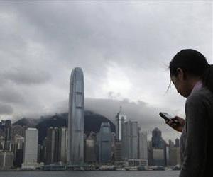 A woman uses her smartphone at the waterfront in Hong Kong Tuesday, June 11, 2013.