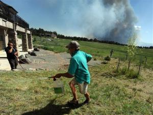 Lynd Fitzgerald sprays fire retardant around a house while a fire burns out of control in the background in Colorado Springs, Colo. on Tuesday afternoon, June 11, 2013.