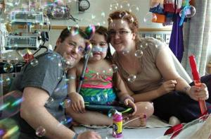 FILE - In this May 30, 2013 file photo provided by the Murnaghan family, Sarah Murnaghan, center, celebrates the 100th day of her stay in Children's Hospital of Philadelphia with her father, Fran, left, and mother, Janet. The 10-year-old suburban Philadelphia girl received a lung transplant there Wednesday, June 12,...
