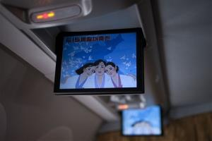 In this Friday June 14, 2013 photo, a music video about a song called Reunification, June 15th is shown on screens of an Air Koryo jet while on its way from Beijing to Pyongyang, North Korea. Korean on the screen read Celebration for the June 15 joint-declaration. Late North Korean...