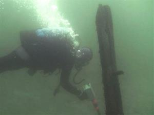 An image from a video shows a diver passing timbers protruding from the bottom of Lake Michigan that were discovered by Steve Libert.