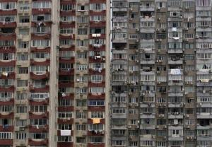 A man looks out from the window of his home at his apartment complex in Shanghai, China.