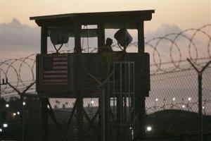 A US soldier keeps watch from a guard tower overlooking the Camp Delta detention center at  Guantanamo Bay.