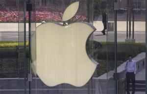 A man smokes near the logo of Apple in Shanghai, China, Tuesday, April 2, 2013.
