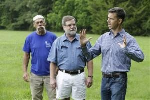 Martin Gallivan, College of William professor, right, gestures as Pamunkey Indian Jeff Brown, left, and  Randolph Turner, retired state archaeologist, center listen during a tour of a farm field overlooking the York River in  Gloucester, Va., Monday, June 17, 2013.